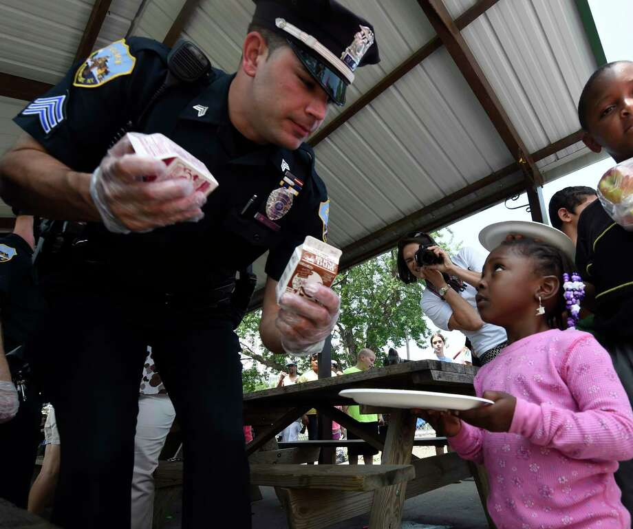 Schenectady police Sgt. Jeffrey McCutcheon serves lunch to Trinity Grace, 3,  at Jerry Burrell Park Wednesday afternoon July 8, 2015 during the Free Summer Lunch program Kickoff event hosted by the Schenectady Inner City Ministry in Schenectady, N.Y.     (Skip Dickstein/Times Union) Photo: SKIP DICKSTEIN / 00032338A