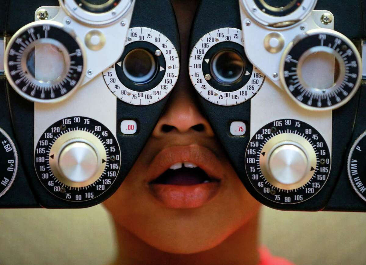 Chaise Perry, 8, looks through a phoropter to get his new prescription during free vision screening Wednesday in in Cypress.