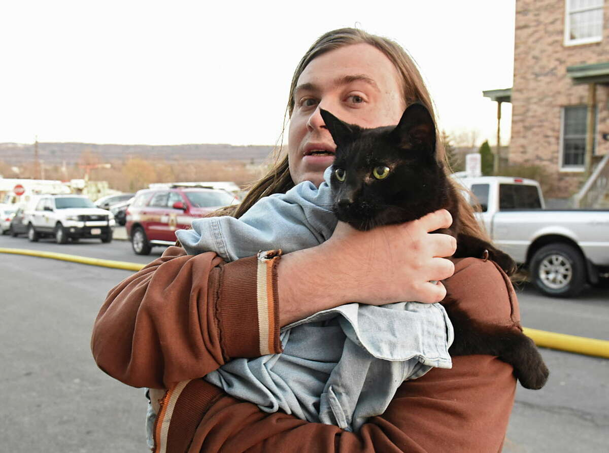 Displaced Cohoes resident Alex David carries his cat Panther to safety as firefighters from around the region work to control a multi-structure fire on Remsen Street on Thursday, Nov. 30, 2017 in Cohoes, N.Y. (Lori Van Buren / Times Union)