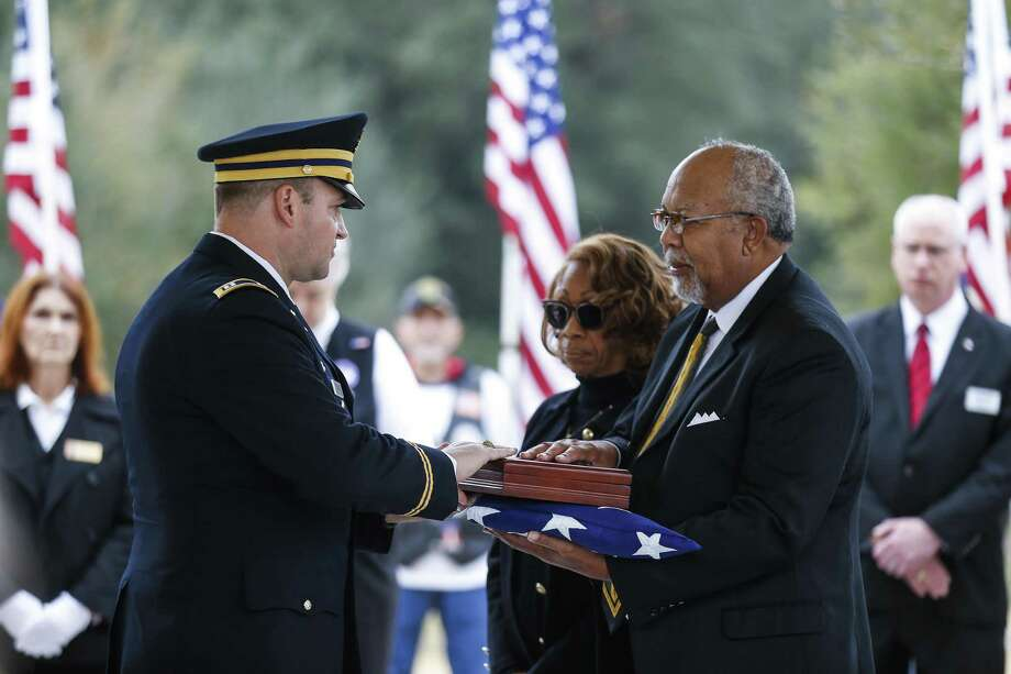 Cpt. Jeffery Hauck (left) presents the flag that was covering Pfc. Lonnie Eichelberger's coffin to his grandnephew, Cheyenne Eichelberger (right) during a funeral service Wednesday at the Houston National Cemetery. Eichelberger's remains were recently identified and returned home after he died in combat in Italy during World War II. Photo: Michael Ciaglo /Houston Chronicle / Michael Ciaglo
