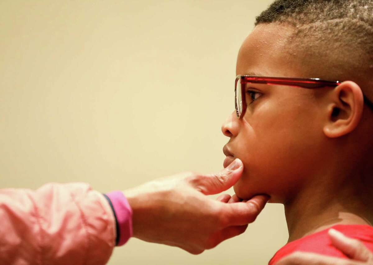 Chaise Perry, 8, gets his new frames checked out by Denetrice Coleman, O.D., during an event to get eye glasses to low-income students from the Houston area, Wednesday, Jan. 10, 2018, in Cypress.