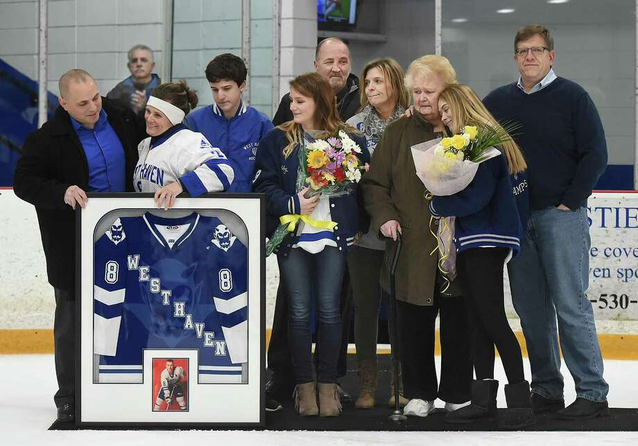 The West Haven hockey team retired the late New Haven police officer and former West Haven hockey player Rob Fumiatti's No. 8 jersey during a ceremony on Wednesday at Bennett Rink in West Haven. Pictured left to right, is Jim Perno, Stacey Fumiatti, Robert's wife, son Vinny Fumiatti, 13, daughter Madelyn Fumiatti, 22, Marguerite Fumiatti, daughter Caitlin Fumiatti, 18, retired Amity hockey coach Gary Lindgren, Rob Fumiatti's sister, Debbie Fumiatti Powers and brother Michael Fumiatti. Photo: Catherine Avalone / Hearst Connecticut Media / New Haven Register