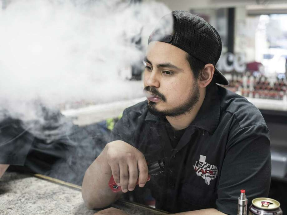 Employee Art Diaz uses his e-cigarette as he works at the Texas Vape Store off of Austin Highway last year in San Antonio. City Council is considering passing a law that would raise the minimum age to buy tobacco products from 18 to 21 years old. Photo: Express-News File Photo / © Matthew Busch