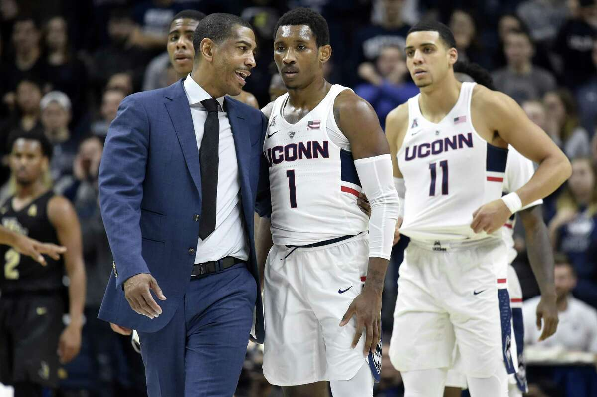 Connecticut head coach Kevin Ollie talks with guard Christian Vital (1) after he was flagrantly fouled by UCF's Dayon Griffin during the first half at Gampel Pavilion in Storrs, Conn., on Wednesday, Jan. 10, 2018.