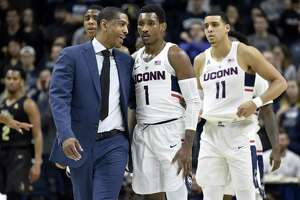 Connecticut head coach Kevin Ollie talks with guard Christian Vital (1) after he was flagrantly fouled by UCF's Dayon Griffin during the first half at Gampel Pavilion in Storrs, Conn., on Wednesday, Jan. 10, 2018. (John Woike/Hartford Courant/TNS)