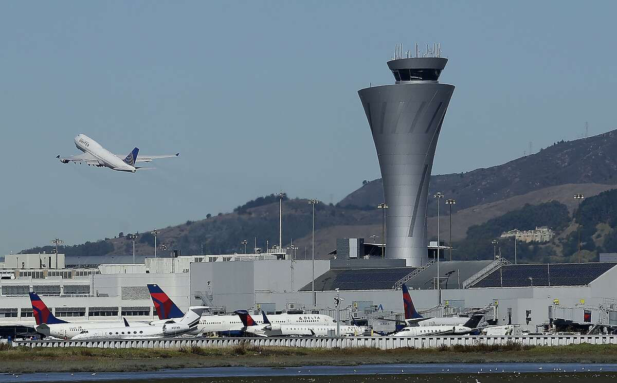 In this Oct. 24, 2017, file photo, the air traffic control tower is in sight as a plane takes off from San Francisco International Airport in San Francisco. The problem of sea level rise along San Francisco Bay is likely to be exacerbated by the sinking shoreline, a new study finds. Treasure Island is slipping nearly 3/4 of an inch per year.