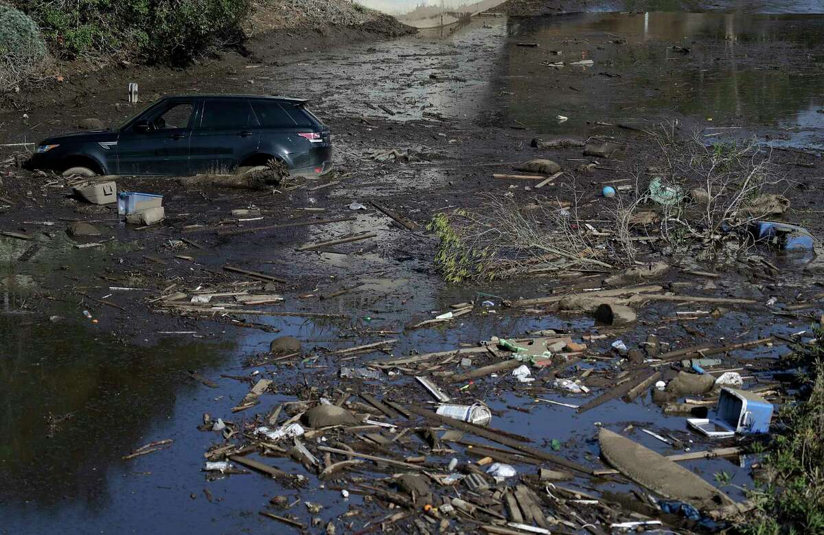 A car sits stranded in flooded water on Highway 101 in Montecito, Calif., Wednesday, Jan. 10, 2018. Dozens of homes were swept away or heavily damaged and several people were killed Tuesday as downpours sent mud and boulders roaring down hills stripped of vegetation by a gigantic wildfire that raged in Southern California last month. (AP Photo/Marcio Jose Sanchez)
