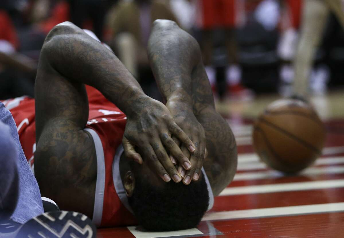 Houston Rockets forward Tarik Black (28) rolls on the floor and covers his face after being fouled by Portland Trail Blazers forward Ed Davis (17) during the third quarter of the NBA game at Toyota Center on Wednesday, Jan. 10, 2018, in Houston. Black scored a dunk and Davis was called Flagrant 1 foul and Black left the court due to concussion protocol after this play. ( Yi-Chin Lee / Houston Chronicle )