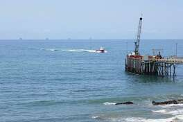 FILE- This May 16, 2015 photo shows oil drillings offshore of a service pier in the Santa Barbara Channel off the coast of Southern California near Carpinteria. Opposition to the Trump administration's plan to expand offshore drilling mounted Wednesday, Jan. 10, 2018. The plan could open up federal waters off the California coast for the first time in more than three decades. The Channel is one of those areas that could open up. (AP Photo/John Antczak, File)