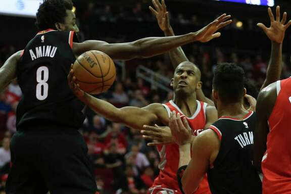 Rockets guard Chris Paul, center, overcomes the defense of the Blazers' Al-Farouq Aminu, left, and Evan Turner to get off a shot during the fourth quarter.