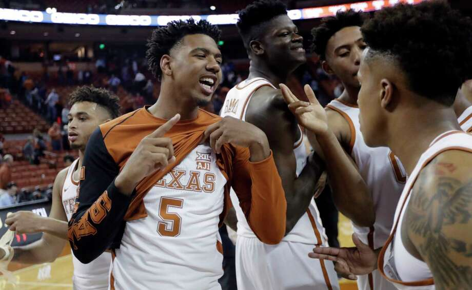 Royce Hamm Jr., left, shows the patch Texas is wearing in support of teammate Andrew Jones as the Longhorns start to celebrate their victory Wednesday night. Photo: Eric Gay, STF / Copyright 2018 The Associated Press. All rights reserved.