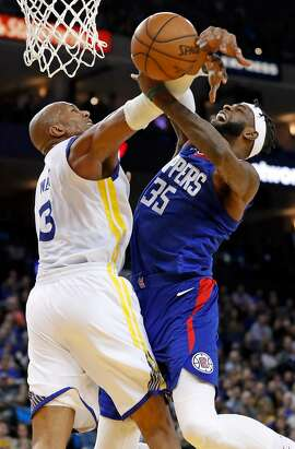 Golden State Warriors' David West fouls Los Angeles Clippers' Willie Reed in 4th quarter during Clippers' 125-106 win in NBA game at Oracle Arena in Oakland, Calif., on Wednesday, January 10, 2018.