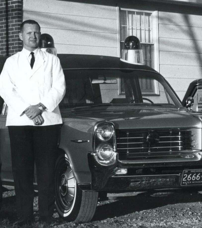 This is Dick Ware posing with the Ware-Smith combination ambulance-hearse provided by Tom McArdle. Gary Johnson remembers delivering a baby in the ambulance before they could get to the hospital and wrapping the baby in a towel.