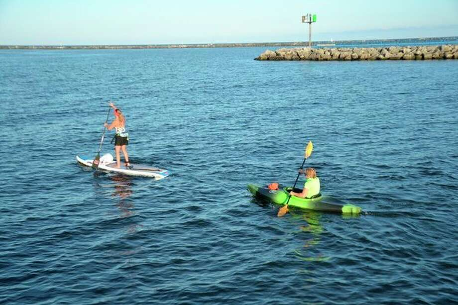 Paddlecraft, such as this stand-up paddle (SUP) board, left, and sit-in kayak, would be required to be registered under a proposal being floated by the Michigan State Waterways Commission.(Steve Griffin/file photo for Hearst Michigan)