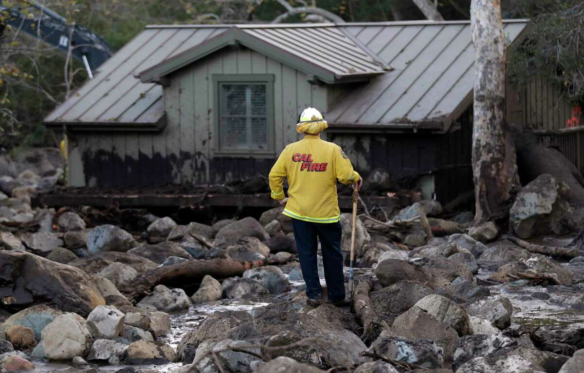 A firefighter walks among the rocks and mud left by a mudslide Wednesday, Jan. 10, 2018, in Montecito, Calif. Anxious family members awaited word on loved ones Wednesday as rescue crews searched grimy debris and ruins for more than a dozen people missing after mudslides in Southern California destroyed houses, swept cars to the beach and left more than a dozen victims dead.