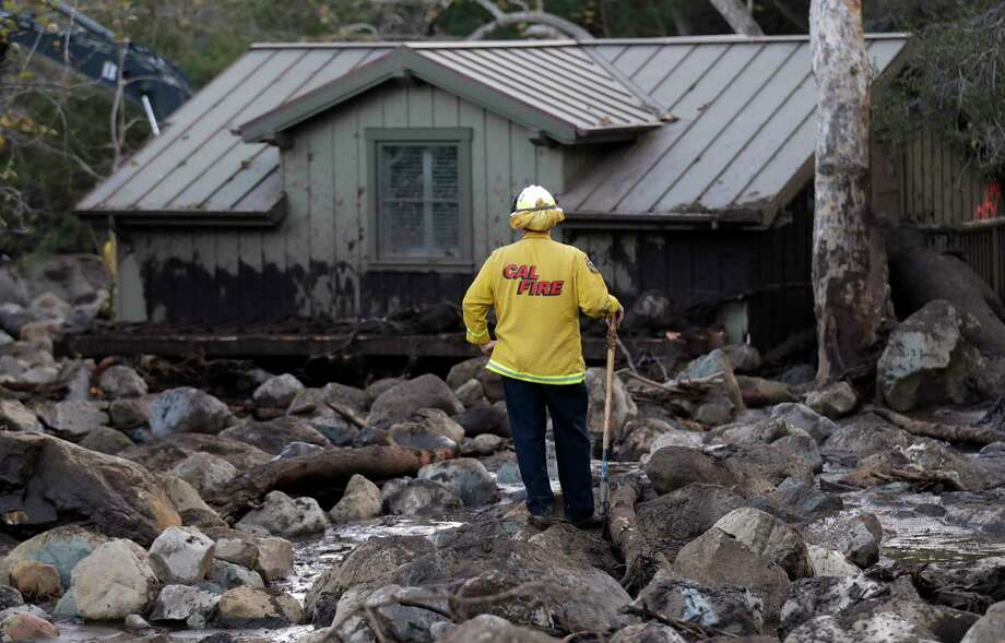A firefighter walks among the rocks and mud left by a mudslide Wednesday, Jan. 10, 2018, in Montecito, Calif. Anxious family members awaited word on loved ones Wednesday as rescue crews searched grimy debris and ruins for more than a dozen people missing after mudslides in Southern California destroyed houses, swept cars to the beach and left more than a dozen victims dead. Photo: Marcio Jose Sanchez, AP / Copyright 2018 The Associated Press. All rights reserved.