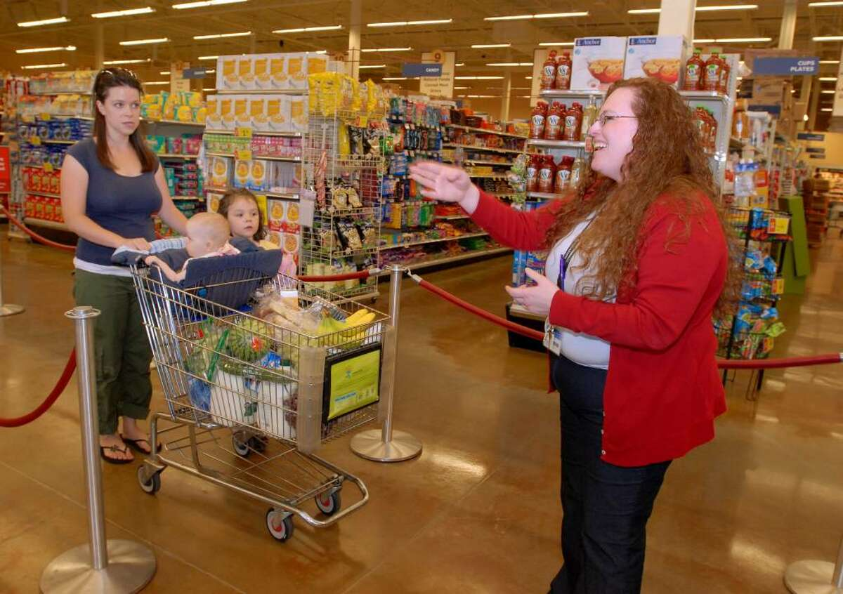 Melissa Murdie and daughters Isabella and Emma Murdie enter the Queue System line at the Ballston Spa Hannaford Supermarket in Milton and are directed to a register with the shortest line by Hannaford's Jennie Paddock. The test system is designed to speed the checkout process, the company says. (Luanne M. Ferris / Times Union)