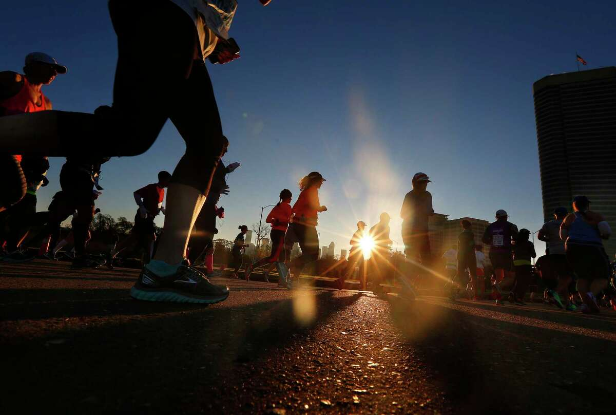 Runners cross Memorial Drive on Waugh Drive while the sun rises over downtown during the opening miles of the Chevron Houston Marathon, Sunday, Jan. 17, 2016, in Houston. ( Mark Mulligan / Houston Chronicle )