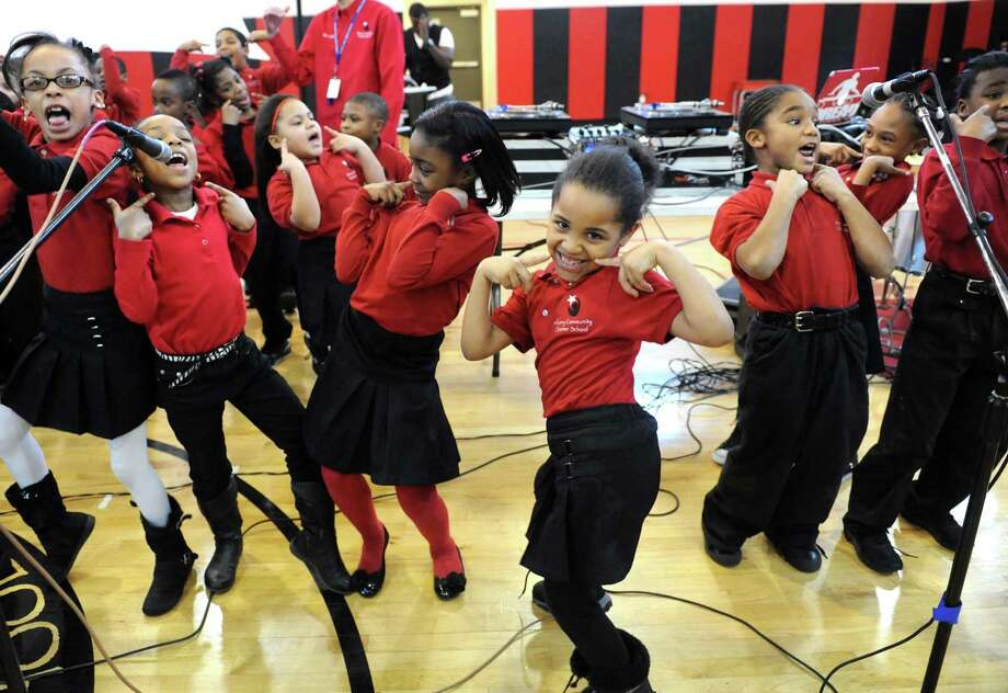 """Anavie Hicks, center, joins classmates in singing, """"I Celebrate MLK""""  during a Remembering and Celebrating Dr. Martin Luther King Jr. program at the Albany Community Charter School on Friday Jan.18,2013 in Albany, N.Y. (Michael P. Farrell/Times Union) Photo: Michael P. Farrell / 00020823A"""