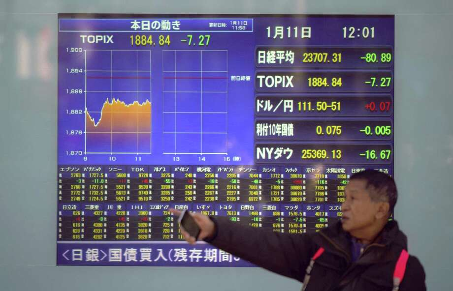 A man stands in front of an electronic stock board showing Japan's Nikkei 225 index and other information at a securities firm in Tokyo Thursday, Jan. 11, 2018. Asian stock markets were lower on Thursday after Wall Street posted its first loss this year. Reports that China may slow its purchases of U.S. government bonds weighed on investor sentiment. Photo: Eugene Hoshiko /Associated Press / Copyright 2018 The Associated Press. All rights reserved.