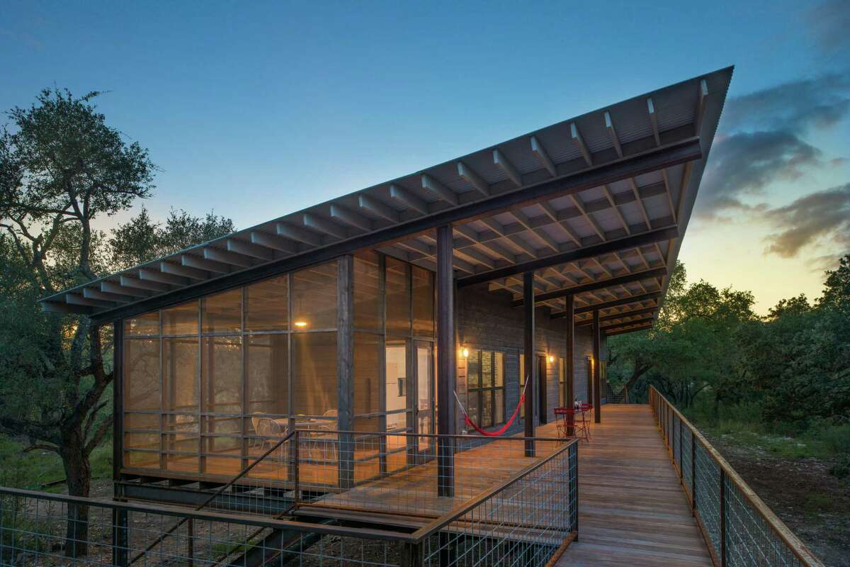 Winner of an American Institute of Architects 2017 design award, the cabin designed by Candid Rogers Architect is a family retreat on the Sabinal River near the small Hill Country town of Utopia. The cabin is powered via a solar-panel system and propane. It has two bedrooms, two full baths (plus an outdoor bath tub), a kitchen and living room, a screened porch and a long, wide porch facing the river. Because it is in the flood plain, the cabin was built on a steel I-beam structure.