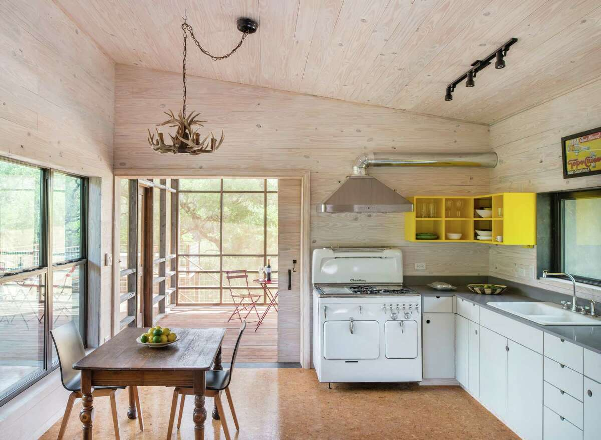 The kitchen, with a restored 1950s Chambers stove converted to propane gas, is an airy room with walls of whitewashed pine cladding and cork-tile floors.
