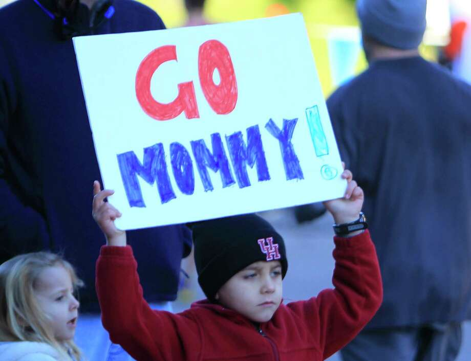 "A young spectator holds a ""Go Mommy!"" sign during the Chevron Houston Marathon, Sunday, Jan. 17, 2016, in Houston. ( Mark Mulligan / Houston Chronicle ) Photo: Mark Mulligan, Staff / © 2016 Houston Chronicle"