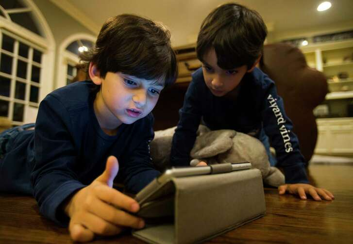 Brothers Adan, 6, and Joaquin, 4, play with an HISD supplied language app that allows them to practice Arabic, Wednesday, Jan. 10, 2018, in Houston. The boys' parents, Omar and Mikhal Abou-Sayed, are careful to limit the amount of screen time their three children, Adan, 6, Joaquin, 4, and Alina, 2, receive, providing numerous other options around the house.