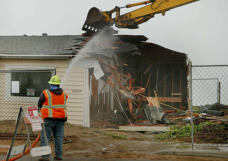 The excavator's huge claw tears at the doomed cliffside dwelling. The former homeowners came from their new place in Contra Costa County to watch their old house get demolished. Photo: Santiago Mejia, The Chronicle