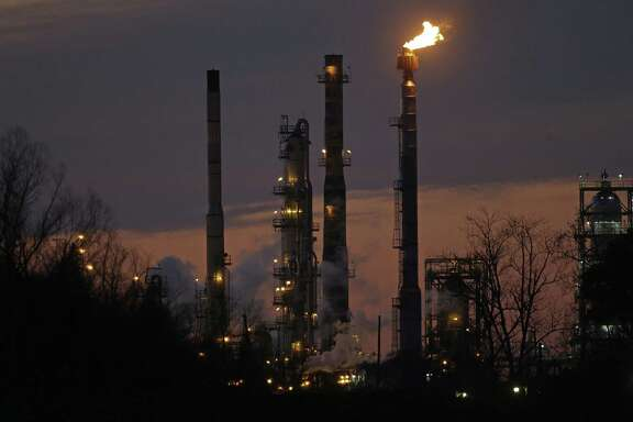 In this Feb. 13, 2015 photo, stacks and burn-off from the ExxonMobil refinery are seen at dusk in St. Bernard Parish, La. Exxon Mobil Corp. this week struck back at several California communities that sued the oil company over the threat of rising sea levels to their jurisdictions, asking a Texas federal judge to allow the oil major to depose municipal officials for a potential countersuit.