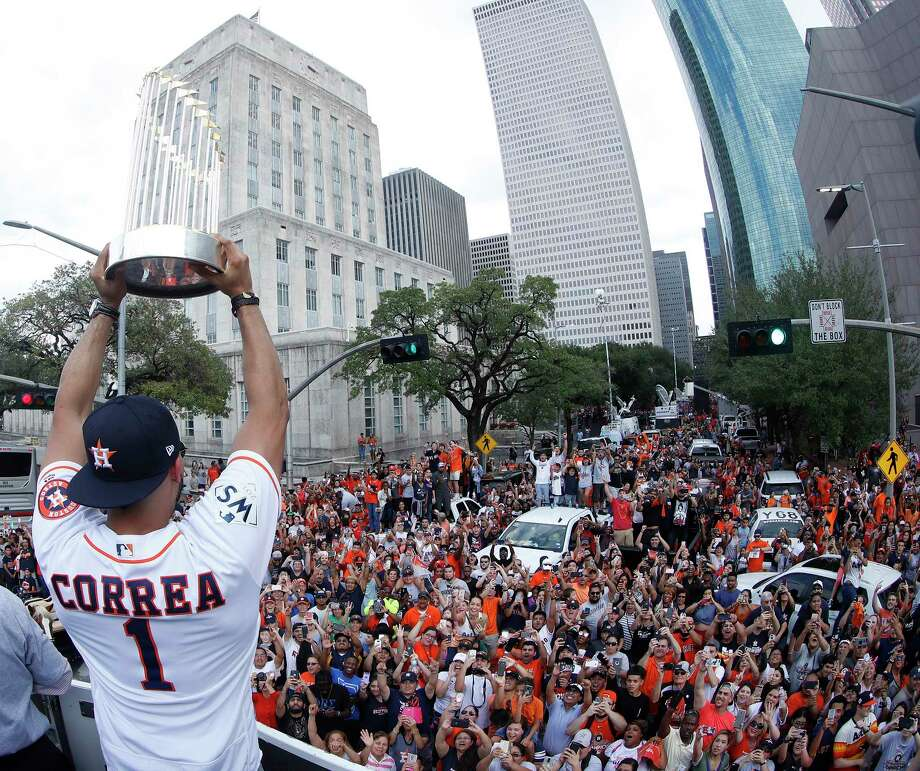 Houston Astros World Series Carlos Correa holds the trophy up near City Hall from the bucket truck of HPD Tower truck 69 during the Houston Astros World Series victory parade downtown on Friday, Nov. 3, 2017, in Houston. ( Karen Warren  / Houston Chronicle ) Photo: Karen Warren, Staff / © 2017 Houston Chronicle
