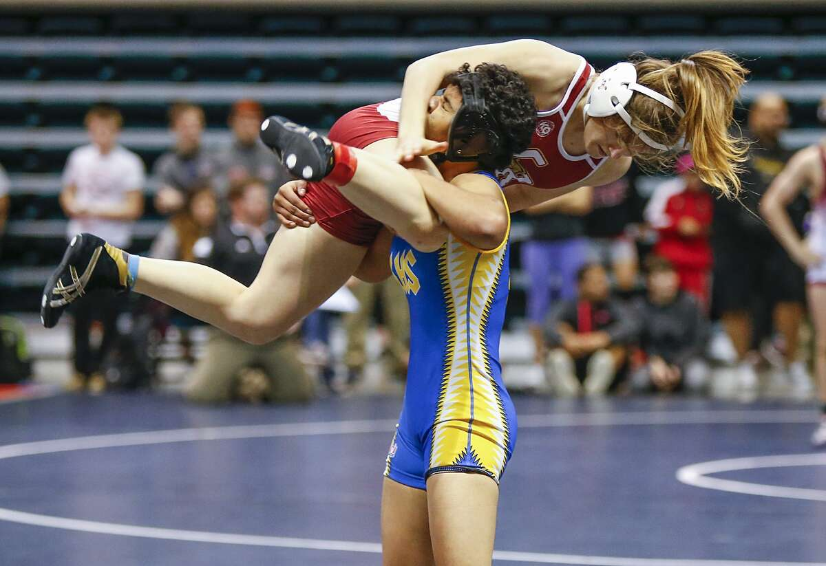 Xochitl Mota-Pettis of Klein attempts a take down of Charlotte Fowler of Cinco Ranch in the championship round of the 110lb class at the 2016 UIL Region III-6A Girls Wrestling Tournament at the Leonard E. Merrell Center in Katy on February 13, 2016.