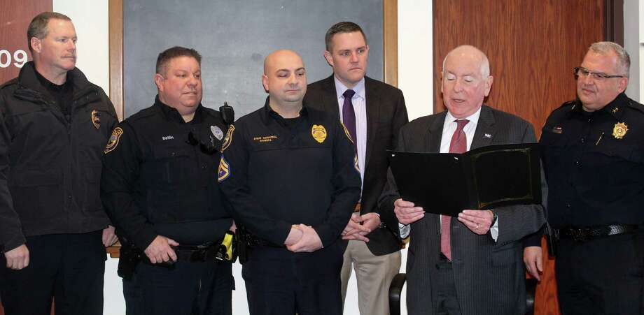 "Westport First Selectmen reads a proclamation announcing Jan. 10 ""Law Enforcement Appreciation Day"" at the Board of Selectmen meeting in Town Hall with members of the police department standing behind him. Photo: Sophie Vaughan /Hearst Connecticut Media"