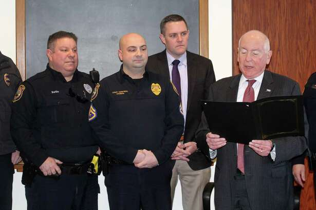 """Westport First Selectmen reads a proclamation announcing Jan. 10 """"Law Enforcement Appreciation Day"""" at the Board of Selectmen meeting in Town Hall with members of the police department standing behind him."""