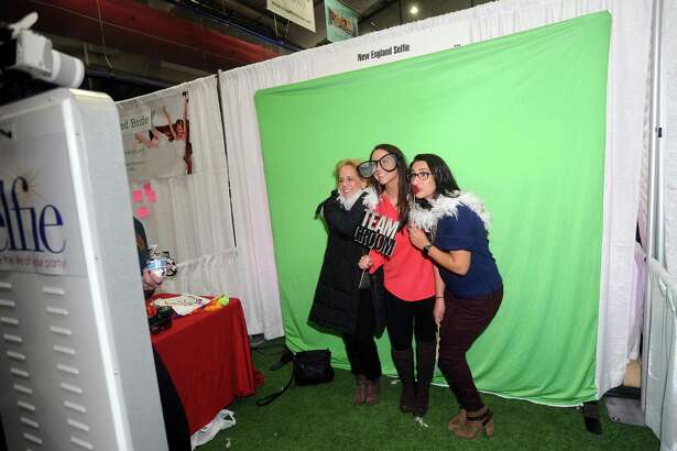 Stamford resident Kristin O'Connor, center, takes a photobooth picture with friend Taylor Funaro, right, and mom Darcy O'Connor at the New Canaan-based New England Selfie during the Connecticut Bridal & Wedding Expo inside Chelsea Piers in Stamford on Jan. 7. New England Selfie was just one of dozens of companies at the expo that can be hired and used for weddings.