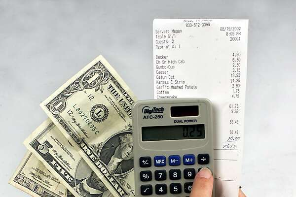 Hands using a calculator to figure a tip while holding money and a receipt. PHOTO BY JUANITO GARZA / STAFF