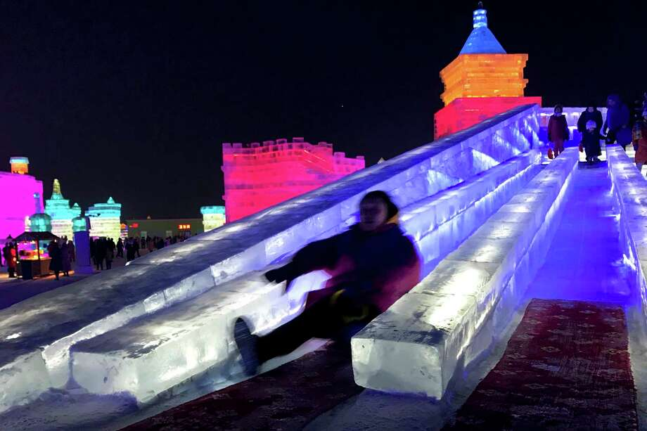 File- This Jan. 5, 2017, file photo shows visitors playing slide on a castle-like structure made from blocks of ice at the annual Harbin International Ice and Snow festival in Harbin, northeastern's China's Heilongjiang province. (AP Photo/Helene Franchineau, File) Photo: Helene Franchineau / Copyright 2017 The Associated Press. All rights reserved.