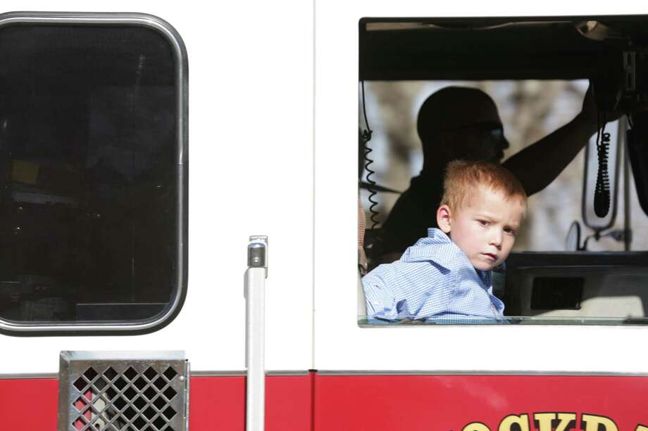Ryland Ward, the 6 yr old boy that was shot four times in the Sutherland Springs massacre, rides in a Stockdale fire truck with Rusty Duncan, the fire fighter that rescued him, on Thursday, Jan. 11, 2018. Ward was released from the hospital and on his way home accompanied by a long procession of first responders. Photo: Bob Owen, Staff / San Antonio Express-News / San Antonio Express-News