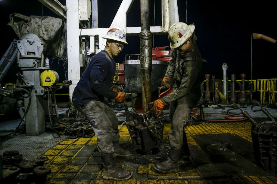 Helmerich & Payne motor man Michael Palmer, left, and floor hand Travis Palmer, right, move equipment as a section of pipe is drilled into the ground for oil and gas extraction on a Diamondback Energy lease Wednesday, Sept. 14, 2016 outside of Midland. ( Michael Ciaglo / Houston Chronicle ) Photo: Michael Ciaglo/Houston Chronicle