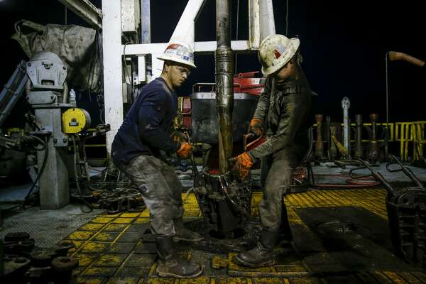 Helmerich & Payne motor man Michael Palmer, left, and floor hand Travis Palmer, right, move equipment as a section of pipe is drilled into the ground for oil and gas extraction on a Diamondback Energy lease Wednesday, Sept. 14, 2016 outside of Midland. ( Michael Ciaglo / Houston Chronicle )