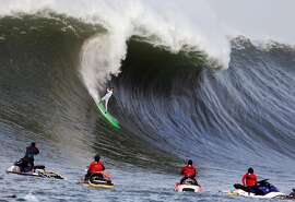 Nic Lamb rides a wave during the third heat of the first round of the Mavericks Invitational big wave surf contest Friday, Jan. 24, 2014, in Half Moon Bay, Calif. (AP Photo/Eric Risberg)
