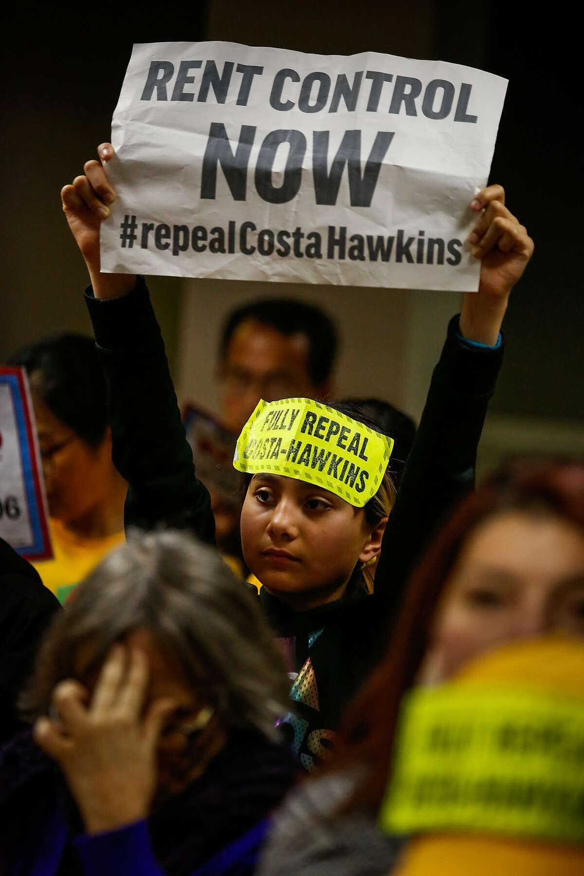Aimee Navarro, 10, holds up a sign during the public comment portion of a hearing on whether or not to repeal the Costa-Hawkins Rental Housing Act at the State Capital in Sacramento, Calif., on Thursday, Jan. 11, 2018. The Costa-Hawkins Rental Housing Act did not pass.