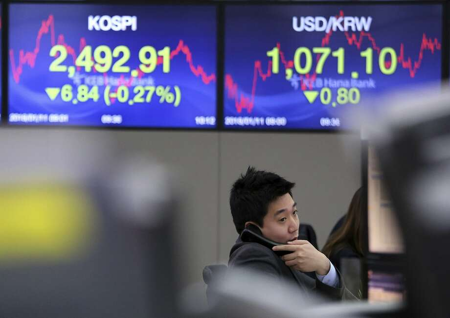 A currency trader talks on the phone at the foreign exchange dealing room of the KEB Hana Bank headquarters in Seoul, South Korea, Thursday, Jan. 11, 2018. Asian stock markets were lower on Thursday after Wall Street posted its first loss this year. Reports that China may slow its purchase of U.S. government bonds weighed on investor sentiment. (AP Photo/Ahn Young-joon) Photo: Ahn Young-joon, Associated Press