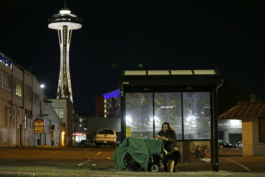 FILE - In this Oct. 30, 2017 file photo, Dave Chung, who says he has been homeless for five years on the streets of California and Washington state, eats a meal before bedding down in a bus shelter in view of the Space Needle in Seattle. On Thursday, Jan. 11, 2018, President Donald Trump's administration announced $2 billion in grants for local programs to deal with homelessness. The funding total is a record for the Continuum of Care grants, but only a small increase over recent years. The announcement comes as the administration is calling for cuts to housing programs and as the West Coast is dealing with a homeless crisis. (AP Photo/Ted S. Warren, File) Photo: Ted S. Warren, Associated Press