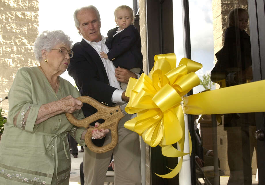 FOR THIS WEEK--Vera Brummett May, left, cuts the ceremonial ribbon to open the May Community Center with County Commissioner Jerry Eversole and his grandson, Hayden Stone Eversole, Thursday, July 10, 2003, in Huffman, Texas.  (Photo by Brett Coomer/Special to the Chronicle)  HOUCHRON CAPTION (07/17/2003):  Vera Brummett May, for whom the May Center in Huffman is named, performs the official ribbon cutting for the renovated center. Harris County Commissioner Jerry Eversole, holding grandson Hayden Stone Eversole, positions the ribbon for the symbolic shears. Photo: BRETT COOMER, STR / FREELANCE
