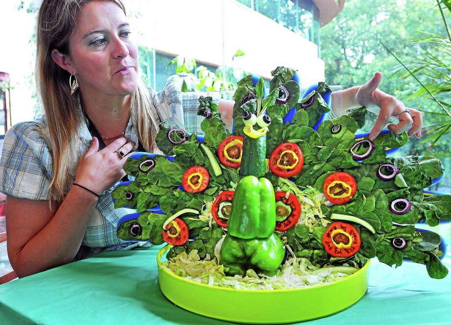 "Jen Myers, senior marketing representative at Subway, showcases in June 2014 her entry in the Milford, Conn.-based company's employee ""veggie art"" contest. Subway was displaced by Wallingford-based Edible Arrangements as the top Connecticut-based franchisor on Entrepreneur's annual ""Franchise 500"" list, with Subway falling out of the top 100. Photo: Peter Casolino / Journal Register Co."
