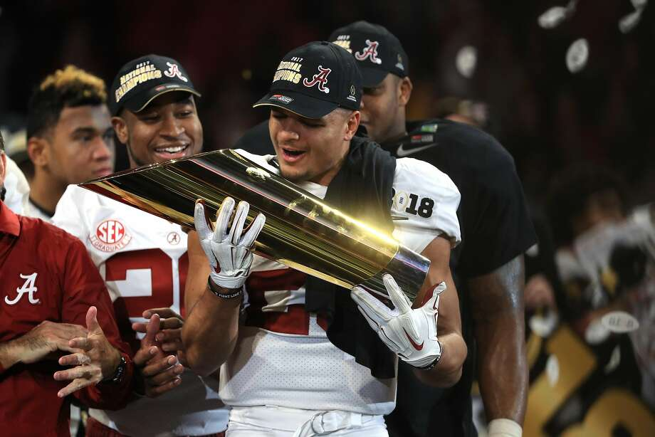 Safety Minkah Fitzpatrick, a projected first-round pick in April's NFL draft, cradles the national title trophy on Monday. Photo: Mike Ehrmann, Getty Images