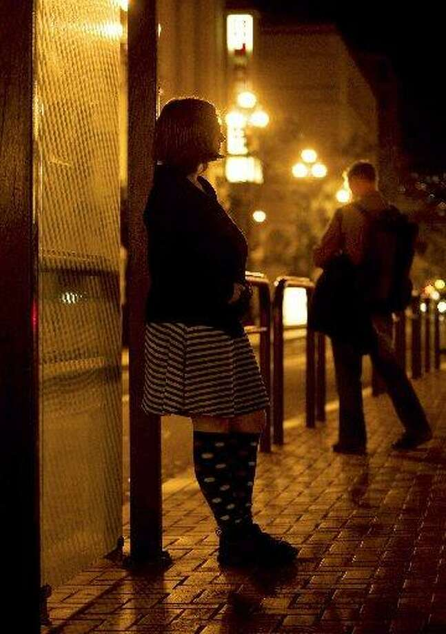 "A sex worker who goes by the name ""Violet"" poses for a picture at a bus stop in downtown San Francisco on Thursday, Oct. 16, 2008. City law enforcement officials on Thursday said they will no longer arrest or charge sex workers for prostitution or petty drug crimes if they are victims or witnesses to violent crime. Photo: AP Photo/Darryl Bush"
