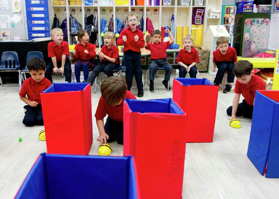 Kindergarteners cheer on classmates as they use Bee-Bots, an interactive programmable floor robot, to navigate a maze during class at Sacred Heart Catholic School, Wednesday, Jan. 10, 2018, in Conroe. Students kindergarten through 8th grade use robots, in addition to other tools, to learn programing and coding skills as part of the school's ongoing emphasis on the fields of science, technology, engineering and math. Photo: Jason Fochtman, Staff Photographer / © 2018 Houston Chronicle
