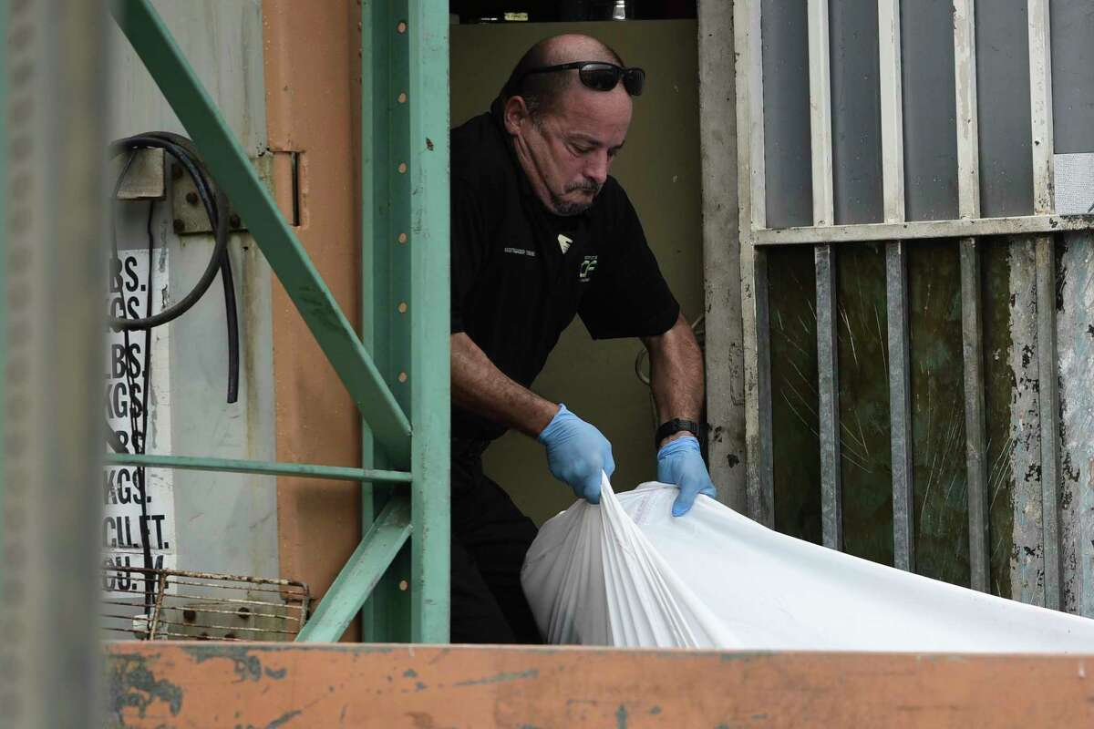 A forensic worker lifts a a body at a crime scene, in San Juan, Puerto Rico, Thursday, Jan. 11, 2018 As the island struggles to recover from Hurricane Maria, it is facing one of the biggest spikes in violent crime in nearly a decade amid a widespread power outage, severe unemployment and an increase in police absences. (AP Photo/Carlos Giusti)